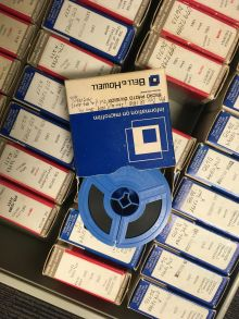 Reel of microfilm atop drawer filled with cartons of microfilm